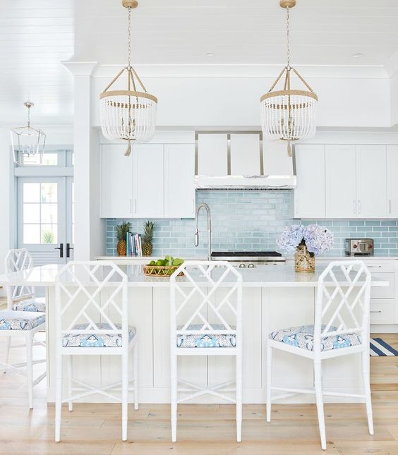 a coastal kitchen with white cabients, a large kitchen island, chic beaded chandeliers, white chairs with printed upholstery