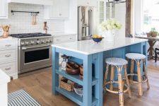a coastal kitchen with white cabinets, a white tile backsplash, a blue kitchen island, rattan stools, blakc metal lamps