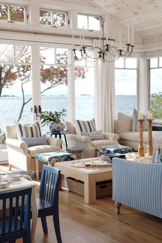 a coastal living room with glazed walls, neutral and striped blue furniture, a wooden table, candleholders and baskets