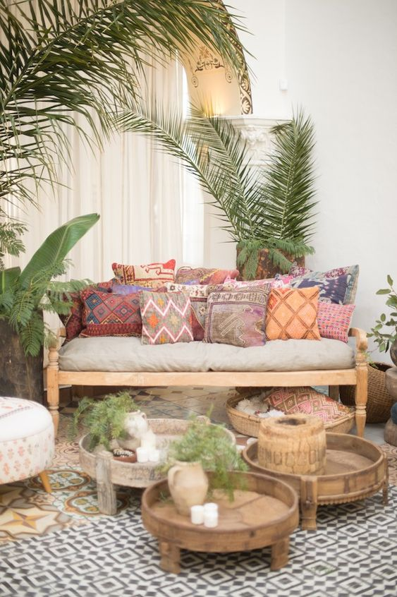 a colorful boho living room with a neutral sofa, colorful pillows, low wooden tables and potted plants