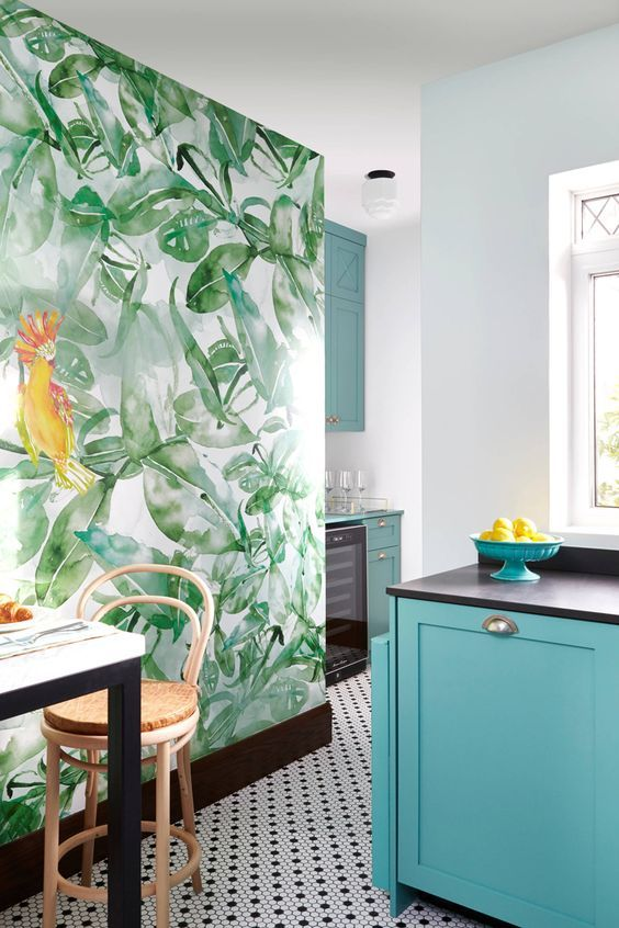 a colorful kitchen with a tropical mural, turquoise cabinets, dark appliances and woven stools looks very tropical like