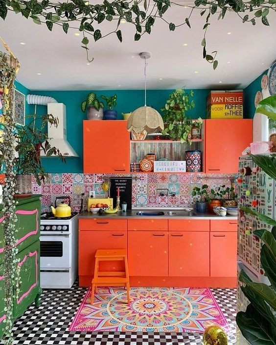 a colorful kitchen with orange cabinets, a mosaic tile floor and a colorful backsplash, teal walls and lots of plants