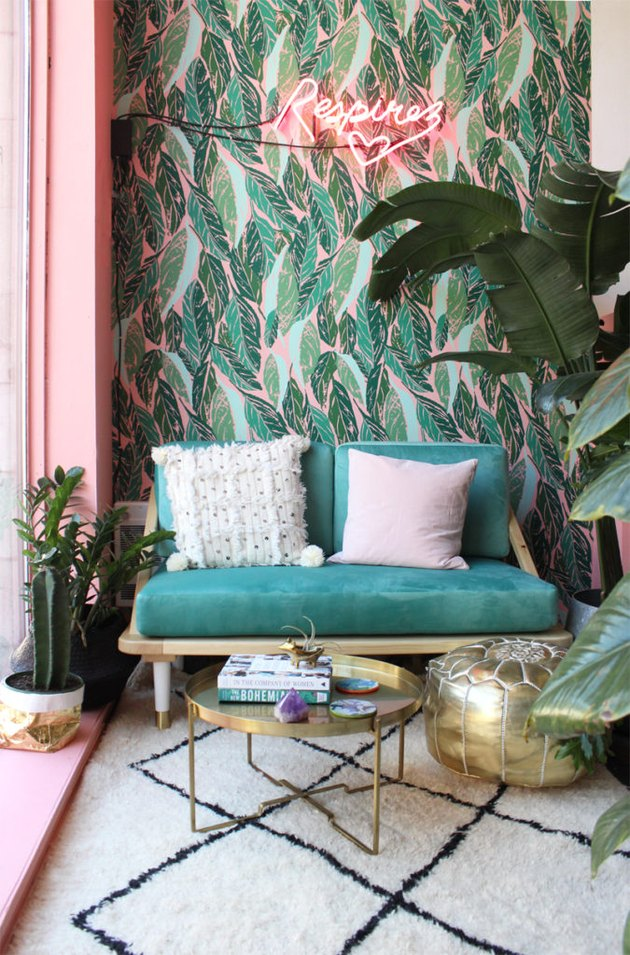 a colorful living room with leaf wallpaper, a pink framed window, potted plants, an emerald sofa and touches of gold