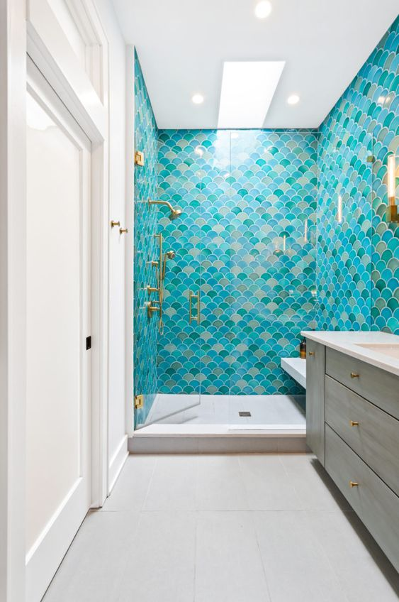 a colorful mermaid bathroom decorated with bright fishscale tiles, a wooden vanity and touches of gold is chic