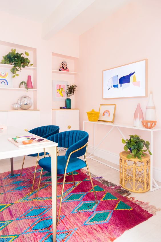 a colorful mid-century modern home office with pale pink walls, a colorful rug, bold blue chairs and artworks and accessories