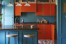 a colorful mid-century modern kitchen in blue and orange, with dark stained wooden countertops and vintage lights