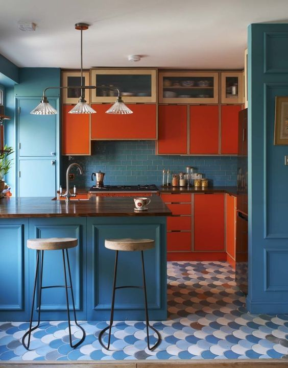 a colorful mid century modern kitchen in blue and orange, with dark stained wooden countertops and vintage lights