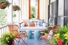 a colorful nautical porch with a suspended daybed with colorful printed pillows, orange rattan chairs, candle lanterns and potted blooms