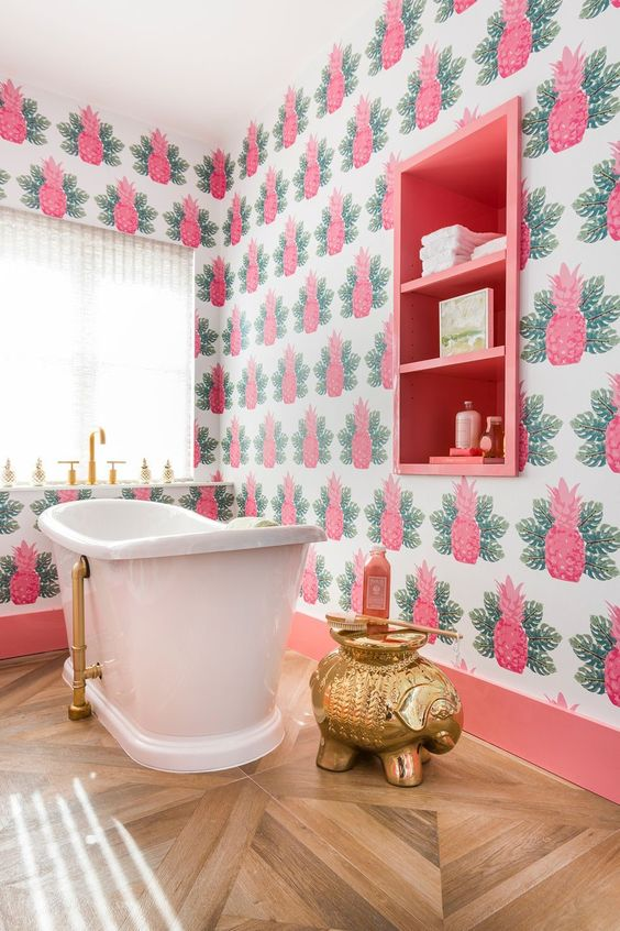 a colorful tropical bathroom with pink pineapple wallpaper, a pink built-in shelf and touches of gold here and there