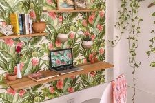 a colorful tropical home office nook with a tropical accent wall, a floating desk and shelves and potted plants