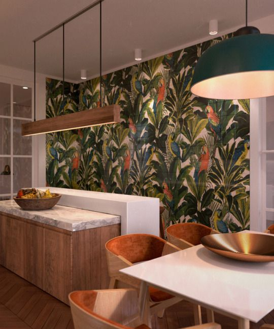 a colorful tropical kitchen with a bold statement wall, a catchy kitchen island with two countertops, a wooden pendant lamp and a cozy dining space