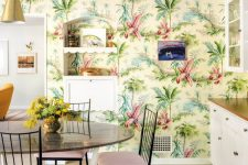 a colorful tropical kitchen with bright printed wallpaper, white cabinets, a round table and pink chairs is fun and cool