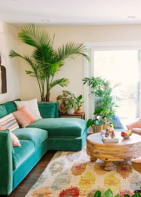 a colorful tropical living room with an emerald sofa, a colorful boho rug, potted plants and a round wooden table