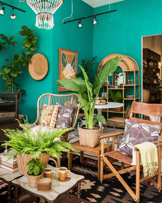 a colorful tropical living room with emerald walls, rattan and leather furniture, a gold mirror, potted plants and bold artworks