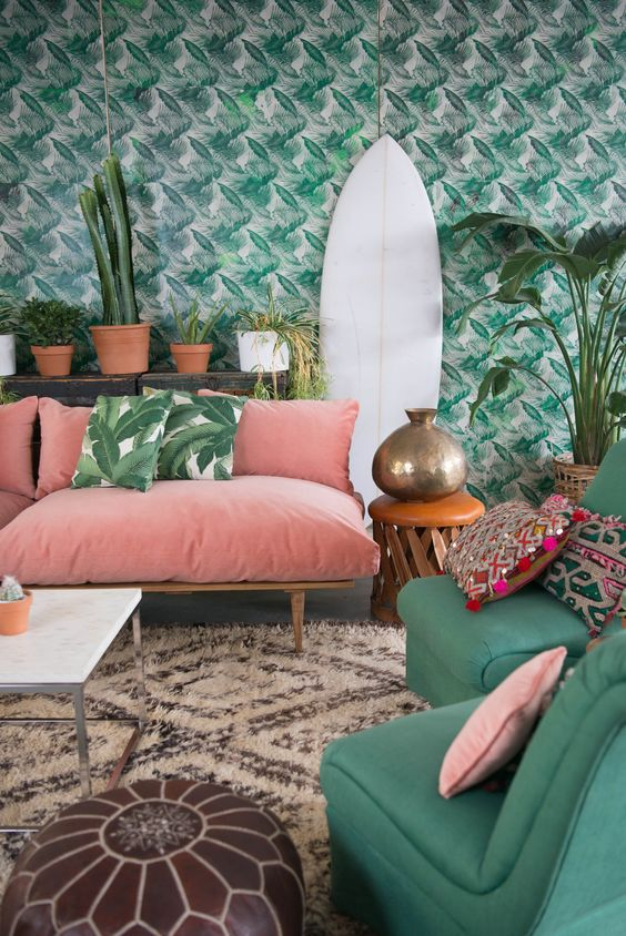 a colorful tropical living space with a tropical print wall, a pink sofa and emerald chairs, tropical pillows and lots of plants