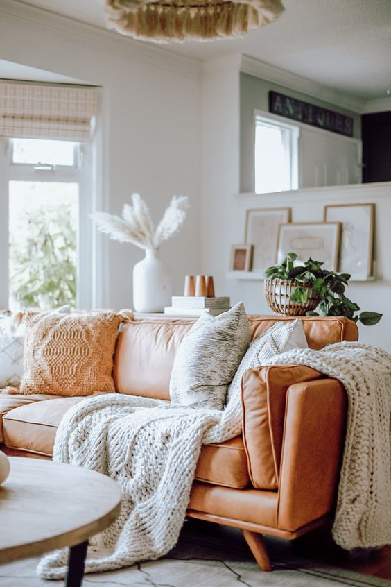 a comfy amber leather sofa styled with knit and crochet pillows and blankets is very cozy and inviting