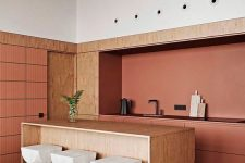 a contemporary burnt orange kitchen with a plywood kitchen island, wooden stools and a black stone countertop