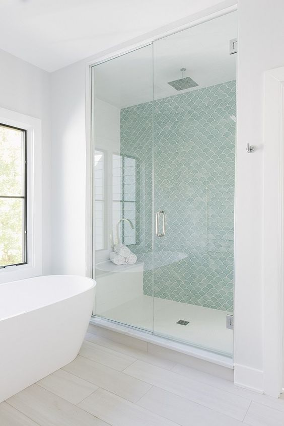 a contemporary coastal bathroom with an aqua fishscale wall, all neutrals around and a free standing tub by the window