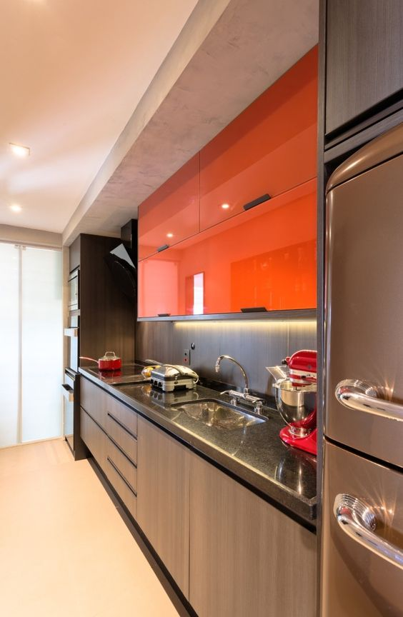 a contemporary dark kitchen spruced up with bold orange sleek upper cabinets and lights looks dramatic