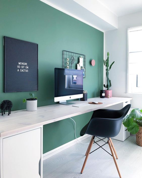 a contemporary home office with a hunter green statement wall, a neutral desk, a gallery wall and potted plants