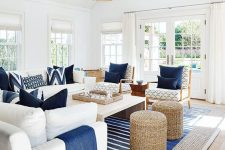 a contrasting coastal living room in white, with creamy furniture, navy pillows and blankets, woven ottomans and rattan lamps