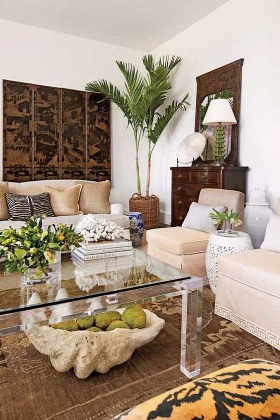 a contrasting tropical living room with white walls, neutral furniture, a dark artwork and sideboard and tropical plants