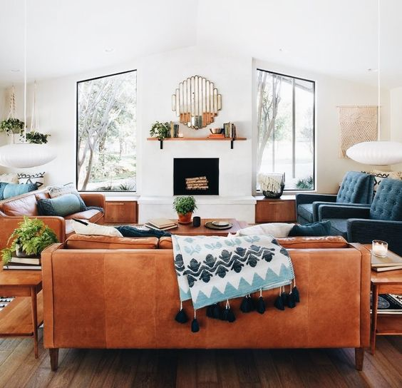 a couple of amber leather sofas and navy chairs create a nice and welcoming conversation pit in mid-century modern style