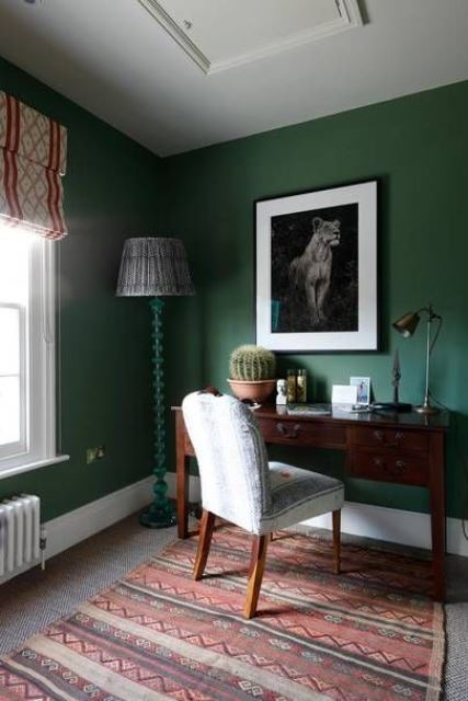 a cozy and stylish home office with hunter green walls, mid century modern furniture, a monochromatic artwork and boho textiles