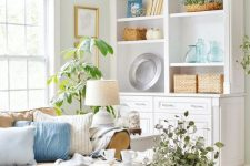 a cozy coastal living room in neutrals, with tan furniture, white and blue pillows, greenery and baskets
