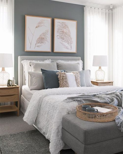 a cozy grey bedroom with grey walls, a dove grey bed and ottoman, layered rugs, light-stained wood