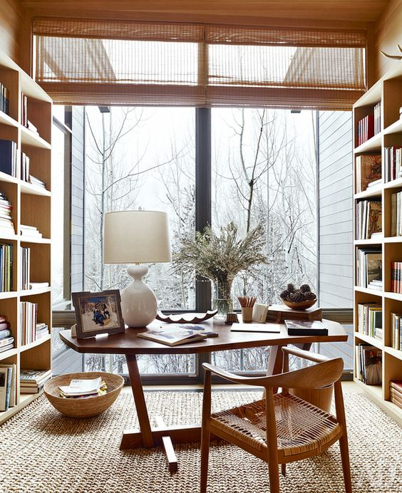 a cozy neutral home office with a gorgeous view and done of wood completely, with a wicker chair and a jute rug is welcoming