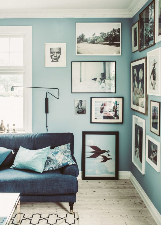 a creative living room with grey blue walls, a navy sofa, blue printed pillows and a gallery wall in the corner