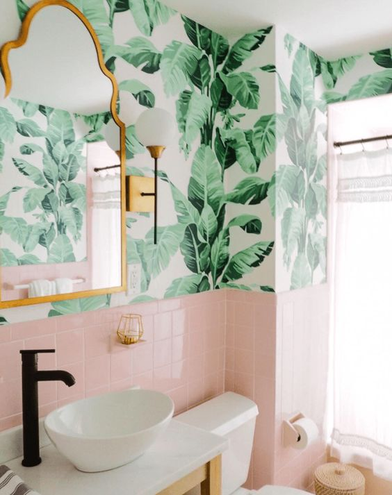 a cute tropical bathroom with banana leaf wallpaper, pink tiles, a copper mirror and a white bowl sink