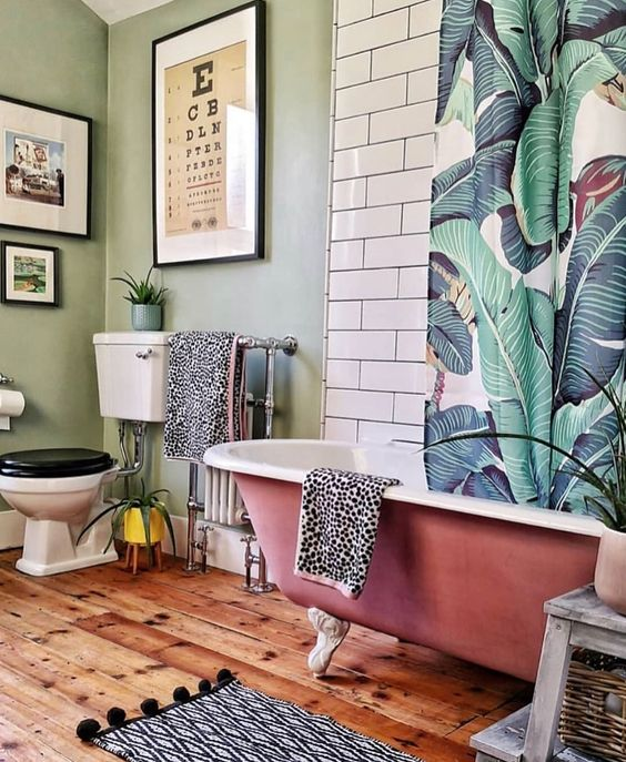 a cute tropical bathroom with green walls, white subway tiles, a pink clawfoot tub, a banana leaf curtain and potted greenery