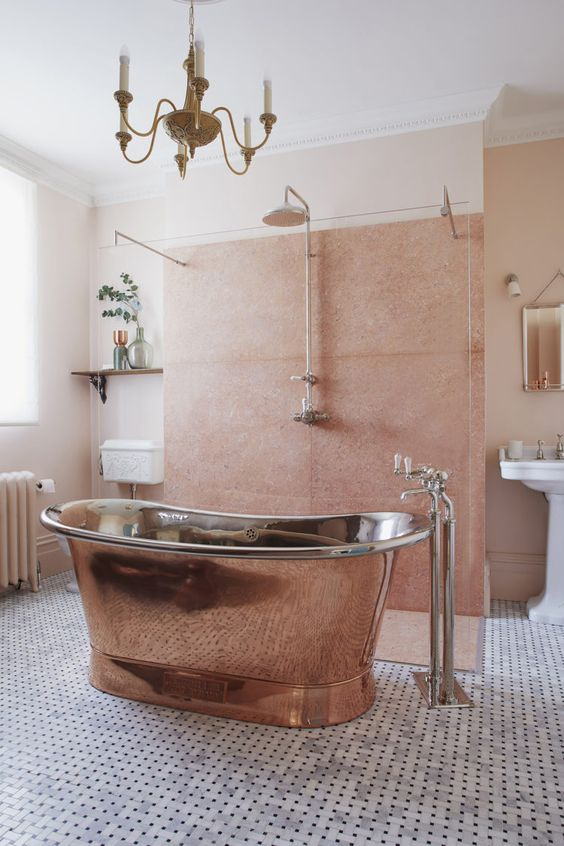 a delicate eclectic bathroom in peachy pink and blush, with a copper bathtub and a vintage chandelier is very welcoming