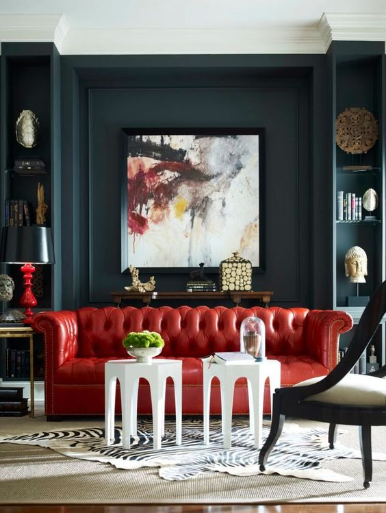 a dramatic living room with dark walls, a bold red leather sofa and a statement artwork that rocks