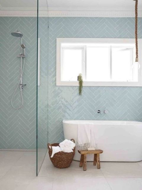 a fresh coastal bathroom with a wall clad with light blue herringbone tiles, a free standing tub, a wooden stool and a basket