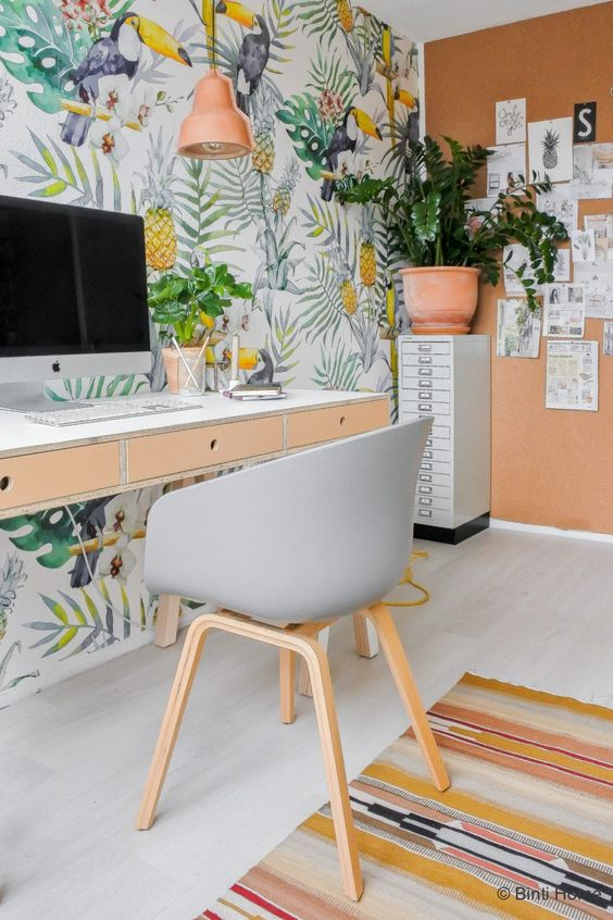 a fun colorful home office with a terracotta wall, a bright pineapple print wall, a colorful rug and tropical plants in pots