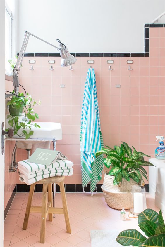 a fun tropical bathroom with pink tiles, a black edge, potted plants and striped towels looks cute