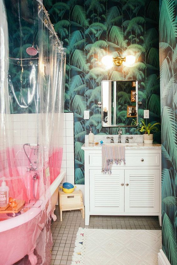 a fun tropical bathroom with tropical wallpaper, a pink tub, sheer and pink curtain, a simple vanity and touches of gold