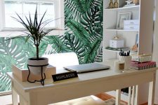 a fun tropical home office with a tropical leaf wall, woven shades, a white leather chair and potted plants