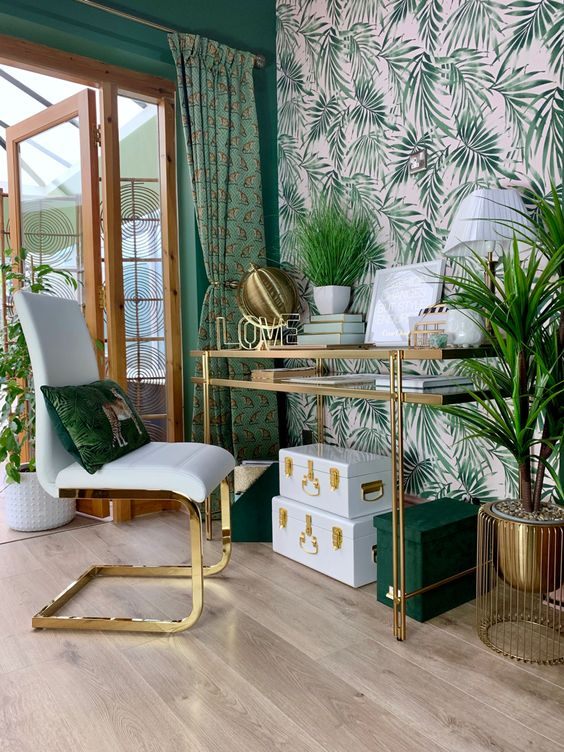 a glam and chic tropical home office with a pink printed wall, green walls, curtains and accessories plus much gold