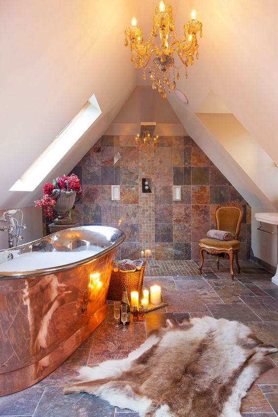 a glam attic bathroom clad with mismatching earthy tiles, with a copper bathtub and a crystal chandelier is amazing
