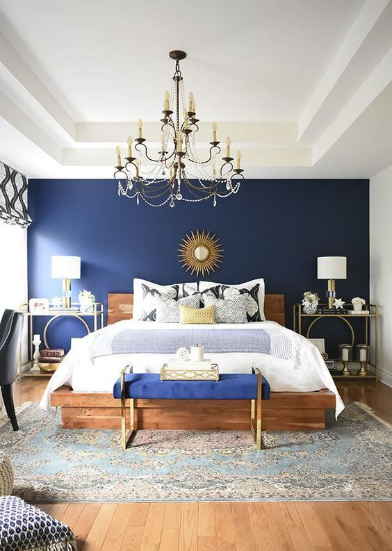 a glam bedroom with a navy wall, a wooden bed, a bold blue bench, gold nightstands and a tray plus a vintage chandelier