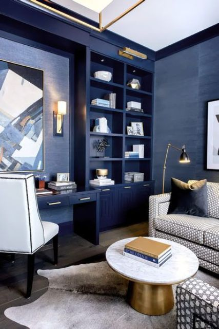 a glam bright blue home office with a built-in storage unit, a built-in desk, white chair and a grey sofa plus gold touches