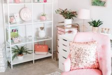 a glam tropical home office with a pink chair with a sequin pillow, a pink storage unit, tropical leaf artworks and a storage unit with pink accessories