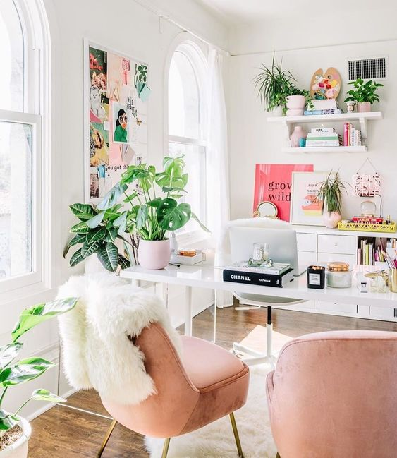 a glam tropical-infused home office with blush chairs, potted greenery, pink accessories and a ffun moodboard