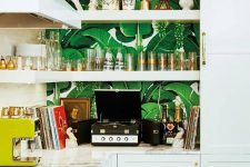 a glam tropical kitchen with banana leaf wallpaper, white cabinets, gold handles and wall sconces for a chic look