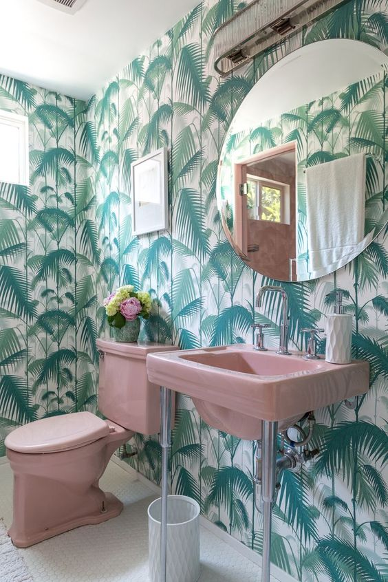 a glam tropical powder room with tropical leaf wallpaper, pink appliances and a large round mirror