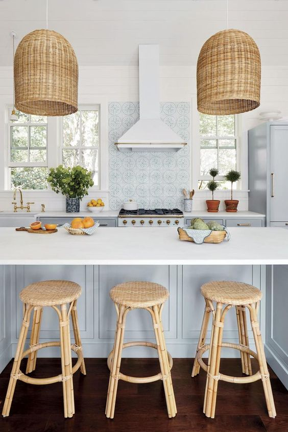 a gorgeous coastal kitchen with light blue cabinets, a light blue kitchen island, rattan stools and woven pendant lamps, potted greenery